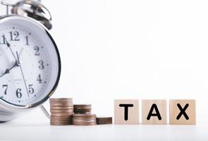 Time to pay tax clock, stacked coins, and wooden block on white background. Taxation and Annual tax concept