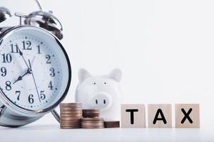 Time to pay tax. Piggybank clock, stacked coins, and wooden block on white background. Taxation and annual tax concept