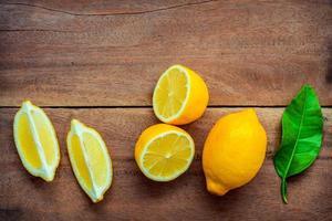 Limones frescos y hojas sobre un fondo de madera foto