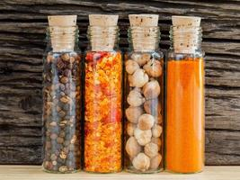 Bottles of spices against a rustic wood background photo