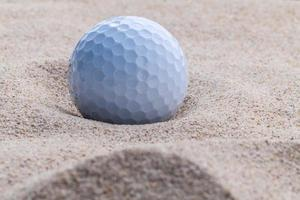 Close-up of a golf ball in sand during the day