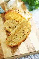 Garlic bread on a wooden base photo