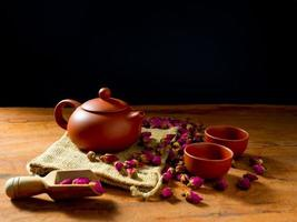 Teapot and teacup with rose tea leaves on wooden table and black background