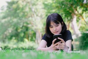A girl sitting in the garden with her phone