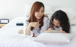 Asian mother and daughter paint together happily on vacation at home photo