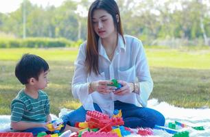 Asian mother and son happily play with toys in the park