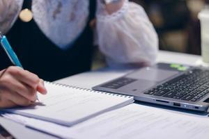 mujer escribiendo notas en un escritorio foto