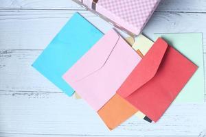 sobres de colores sobre fondo rosa con espacio de copia foto