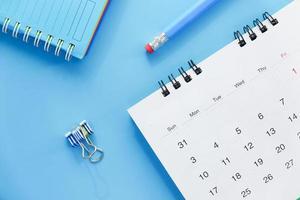 Calendario y lápiz sobre fondo azul. foto