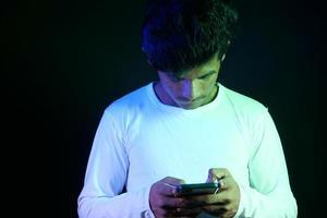 joven jugando en el teléfono con fondo negro foto