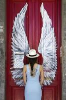 Young woman in front of door with painted wings photo