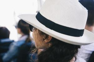 Back view at young woman with white hat