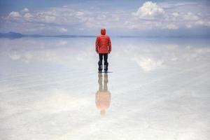 Young man in winter hooded jacket at Salar de uyuni salt flat in Bolivia photo