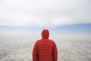 Joven en invierno chaqueta con capucha en el Salar de Uyuni en Bolivia foto