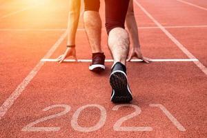 año nuevo o comenzar directamente el concepto. Cerca de un corredor atleta corriendo hacia el éxito y nuevos logros en el camino con inscripción 2021