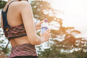 A female runner standing outdoors holding a water bottle, healthy and sport concept