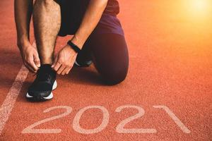 New year or start straight concept. Close up of an athlete runner running to success and new achievements on the path with 2021 inscription