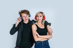 Feliz pareja joven en auriculares escuchando música en el estudio