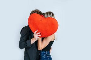 feliz pareja amorosa juntos sosteniendo un corazón rojo