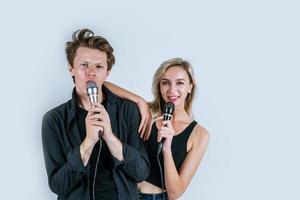 feliz retrato de pareja sosteniendo micrófonos y cantando