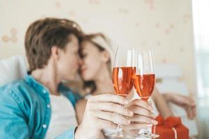 pareja feliz bebiendo vino en el dormitorio
