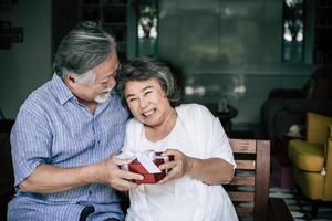 Sonriente marido senior haciendo sorpresa dando caja de regalo a su esposa foto