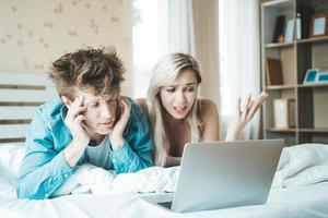 pareja feliz, usar la computadora portátil, computadora portátil, en la cama