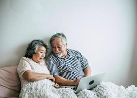 pareja de ancianos hablando y usando la computadora portátil en el dormitorio