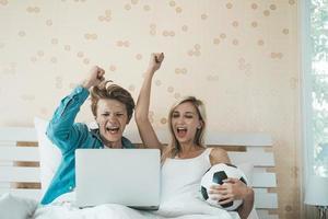 feliz pareja viendo fútbol soccer en la cama