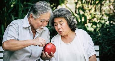 pareja de ancianos cortando y comiendo fruta