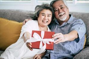 pareja de ancianos sorprende con caja de regalo en el salón