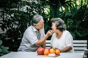 pareja de ancianos jugando y comiendo fruta