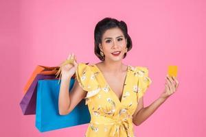 las mujeres de la moda disfrutan comprando con bolsa de compras y tarjeta de crédito