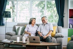 pareja mayor, hablar, y, utilizar la computadora portátil