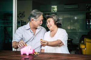 pareja de ancianos hablando de finanzas con hucha foto