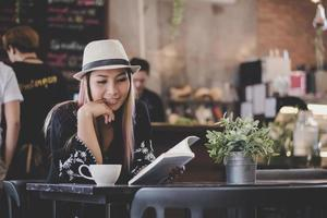 Happy business woman reading a book while relaxing at cafe photo