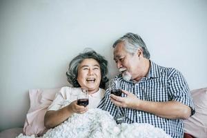 Elderly couple enjoying their anniversary in bedroom photo