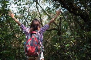 Caminante con mochila de pie en el bosque de una montaña con las manos levantadas