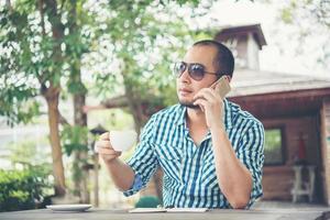 Joven empresario con smartphone mientras trabaja en el jardín de su casa