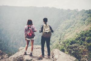 Pareja de excursionistas con mochilas de pie en la cima de una montaña y disfrutando de la vista de la naturaleza