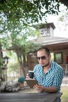 El joven se sienta al aire libre en una mesa de madera y se relaja con una tableta