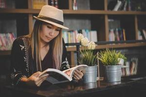 Feliz mujer de negocios leyendo un libro mientras se relaja en el café foto