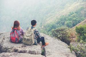 pareja joven disfruta de la vista en el pico de la montaña