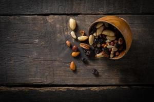 Close-up de frutos secos vertidos de un recipiente sobre fondo de madera