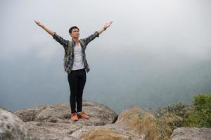 Hiker with backpack standing on top of a mountain with raised hands photo
