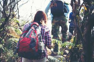Close-up de amigos caminando con mochilas en el bosque desde atrás