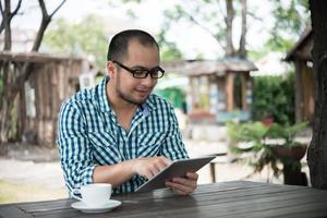 Businessman works on tablet while sitting at wooden table at home photo