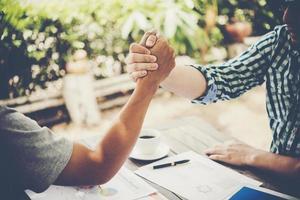 primer plano, de, dos, hombres de negocios, dándose la mano, mientras, sentado, en, el, lugar de trabajo