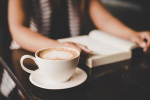 Mujer asiática relajarse y leer un libro en la cafetería. foto