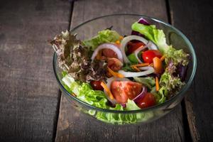 Ensalada de verduras frescas en un tazón de vidrio sobre fondo de madera foto